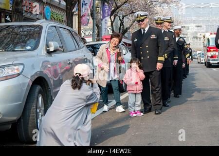 CHINHAE, Republic of Korea (April 05, 2019) Cmdr. Jeremy Ewing, commander, Fleet Activities Chinhae (CFAC) poses for a photo with a family during the 57th annual Jinhae Gunhangje military port festival parade. The festival honors Admiral Yi Sun-sin, a great naval hero of Korea, whose victories still inform the fighting spirit of the ROK Navy. - Stock Photo