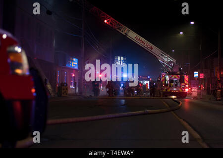 Ontario Canada April 13 2019: Building fire at night with multiple fire trucks and police on scene. - Stock Photo