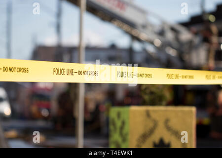 Caution tape at the scene of a fire. Emergency response. Police blocking off the street during an active fire. - Stock Photo