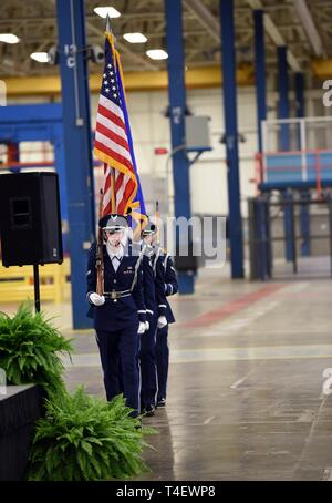 The Robins Air Force Base Honor Guard posts the colors at a gathering in Macon, Georgia, April 5, 2019, in which the announcement of an innovative workforce development approach between the Macon-Bibb Industrial Authority, the Warner Robins Air Logistics Complex at Robins and Central Georgia Technical College was made. This unique partnership proposes to co-locate the 402nd Commodities Maintenance Group sustainment commodities workload from Robins alongside CGTC's educational training programs. If ultimately approved, this partnership will be a first-of-its kind, innovative workplace-based edu - Stock Photo