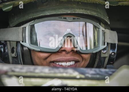 Army Reserve Spc. Kadeesia Lindsey, a chemical, biological, radiological and nuclear (CBRN) specialist and native of Newberry, South Carolina, assigned to the 371st Chemical Company, 457th Chemical Battalion, 415th Chemical Brigade, 76th Operational Response Command smiles before driving her Stryker vehicle and crew onto a gunnery range as part of Operation Gauntlet at Fort Riley, Kansas, April 5. More than 450 Army Reserve Soldiers from around the country are participating in the three-week gunnery exercise to hone crucial platform gunnery skills and increase battlefield lethality. - Stock Photo