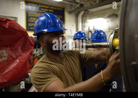 U.S. Navy Aviation Machinist's Mate Airman Quintavious Haugabook, from Fort Lauderdale, Florida, conducts maintenance on a jet engine in the jet shop aboard the aircraft carrier USS John C. Stennis (CVN 74) in the Arabian Gulf, April 6, 2019. The John C. Stennis Carrier Strike Group is deployed to the U.S. 5th Fleet area of operations in support of naval operations to ensure maritime stability and security in the Central Region, connecting the Mediterranean and the Pacific through the western Indian Ocean and three strategic choke points. - Stock Photo