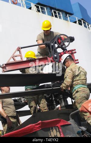 149  CORPUS CHRISTI, Texas – A team of 6th Attack Reconnaissance Squadron, 17th Cavalry Regiment, 4th Combat Aviation Brigade, 4th Infantry Division Soldiers unfold the rotary wings on an AH-64 Apache helicopter at the Port of Corpus Christi, March 28, 2019. The 4th CAB returned from Europe where they deployed in support of Atlantic Resolve, a mission which builds readiness, increases interoperability, and enhances the bonds between ally and partner militaries with multinational training events in Bulgaria, Estonia, Hungary, Latvia, Lithuania, Poland and Romania. About 1,500 pieces of brigade  - Stock Photo
