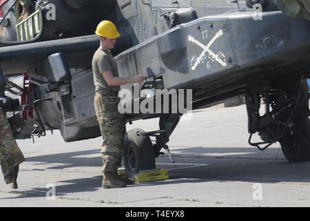 CORPUS CHRISTI, Texas – Pfc. Connor Mitchell, AH-64 attack helicopter repairer, Troop D, 6th Attack Reconnaissance Squadron, 17th Cavalry Regiment, 4th Combat Aviation Brigade, 4th Infantry Division, closes a compartment door on an AH-64 attack helicopter March 28, 2019. The 4th CAB returned from Europe where they deployed in support of Atlantic Resolve, a mission which builds readiness, increases interoperability, and enhances the bonds between ally and partner militaries with multinational training events in Bulgaria, Estonia, Hungary, Latvia, Lithuania, Poland and Romania. About 1,500 piece - Stock Photo