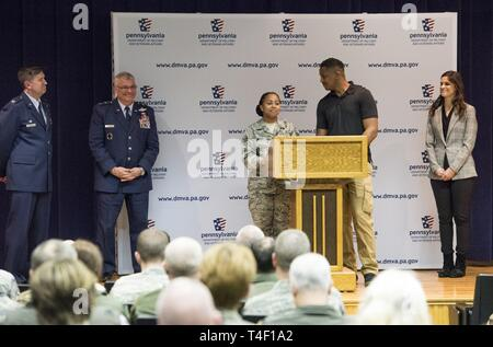 U.S. Air Force Senior Airman Nefertiti Wade along with her husband Adam Wade spoke during the Pennsylvania Adjutant General's press conference at the 171st Air Refueling Wing near Pittsburgh while Col. Mark Goodwill, far left, 171st Air Refueling Wing Commander, Maj. Gen. Tony Carrelli, left, Pennsylvania Adjutant General, and Honorable Natalie Mihalek, right, 40th Legislative District in the Pennsylvania House of Representative listened to the married couple April 5, 2019. The Wade's expressed their appreciation for the proposed Military Family Education Program and how it might benefit their - Stock Photo