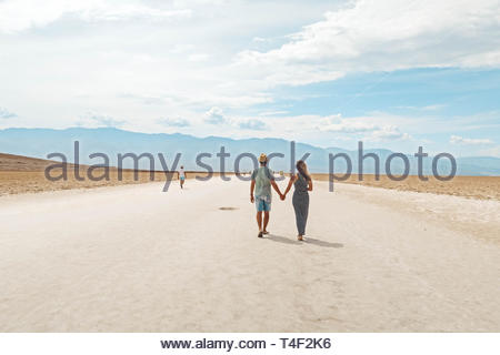 man and woman holding hands while walking in open ground during daytime - Stock Photo