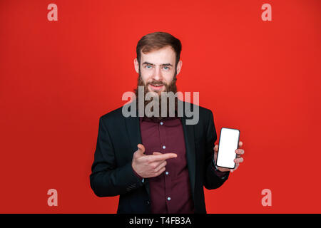 Bearded man pointing with finger at smartphone. - Stock Photo