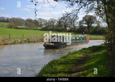 The Oxford Canal meanders through the Warwickshire countryside near the village of Wormleighton as a narrow boat sails along it. - Stock Photo