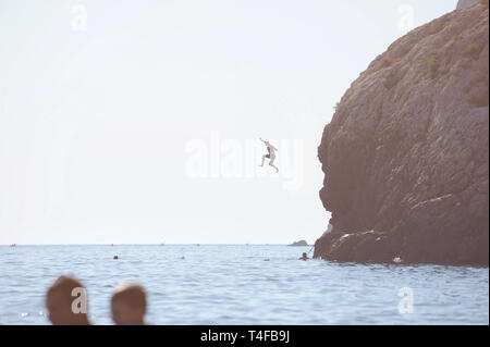brave young man jumping from high rocky mountain into t sea with swimming people - Stock Photo