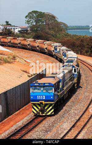 Rail and port operations for managing and transporting iron ore.Train on  rail loop with loaded wagons before discharging ore into port dumper hopper - Stock Photo