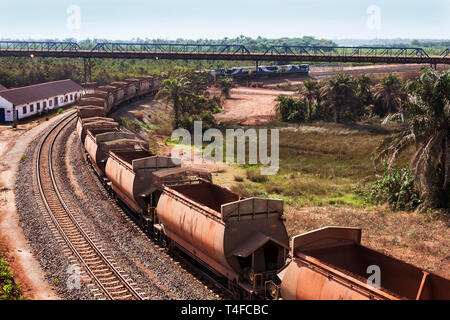 Rail & port operations for managing & transporting iron ore. Train on rail loop under loading jetty conveyor belt after discharge, with empty wagons - Stock Photo