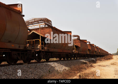 Port operations for managing and transporting iron ore. Railway wagons near port area carrying iron ore before loading onto ships for overseas markets - Stock Photo
