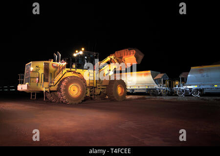 Rail head operations at mine with new wagons on train being loaded with hematite iron ore stock at night before travelling to port for sale overseas - Stock Photo