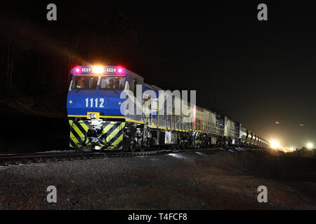 Iron ore mine rail head operations. Front of train at night loaded with hematite stock before travelling to port to discharge load for sale overseas - Stock Photo