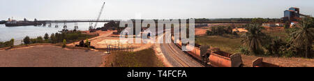 Rail & port operations for managing and transporting iron ore. Ship at loading jetty at end of conveyor belt & ore train on rail loop after discharge. - Stock Photo