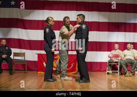 A graduate of Marine Corps Police Academy West is presented with a badge on stage at Marine Corps Air Station Miramar, Calif., April 9. Prior to graduating, recruits go through a 24 week physical training program before earning their badge as an officer in law enforcement. - Stock Photo