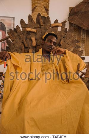 man in yellow rob e sits on brown throne - Stock Photo