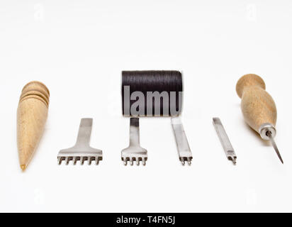 Leather working tools isolated on white background. Chisel set (one two three and four prong wooden burnisher stitching awl and black thread. - Stock Photo