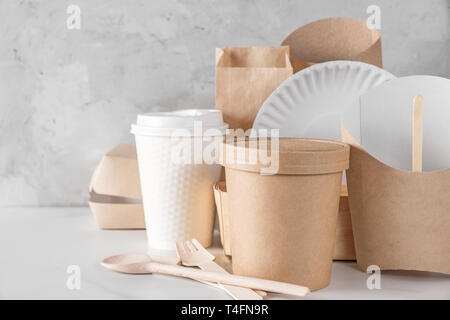 eco friendly disposable dishes made of bamboo wood and paper on white marble background. Draped spoons, fork, knives, plate with paper cups. recycling - Stock Photo