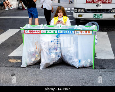 Seoul, South Korea - June 17, 2017: Woman sitting near waste sorting containers with colored inscriptions for plastic, glass bottles and paper. - Stock Photo