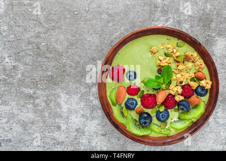 bowl of green matcha tea smoothie with fresh berries, fruits, granola, nuts and seeds for healthy vegan breakfast. diet food concept. top view - Stock Photo