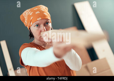 Female carpenter examining plank for diy woodwork project in carpentry workshop, selective focus - Stock Photo
