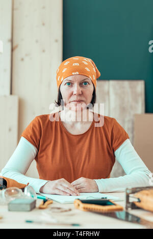 Portrait of confident female carpenter wearing headscarf bandana in small business woodwork workshop - Stock Photo