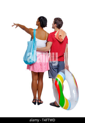 Back view of a an international pointing couple with an inflatable circle and beach accessories. beautiful friendly girl and guy together. Rear view p - Stock Photo