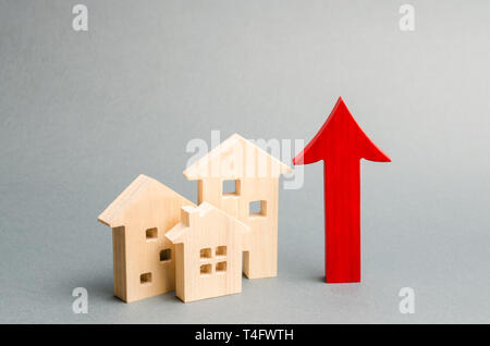 Miniature wooden houses and red arrow up. The concept of increasing the cost of housing. High demand for real estate. The growth of rent and mortgage  - Stock Photo