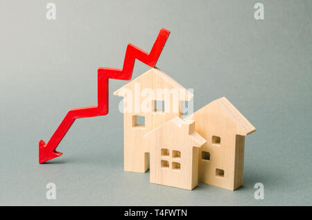 Miniature wooden houses and a red arrow down. The concept of low cost real estate. Lower mortgage interest rates. Falling prices for rental housing an - Stock Photo