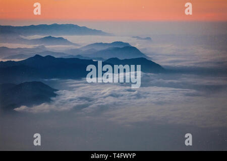 Photo of a high mountain peaks on the sunrise in Africa, Kilimanjaro.Red and peach colors of the sky, white clouds wrapping black mountain range. Peak - Stock Photo