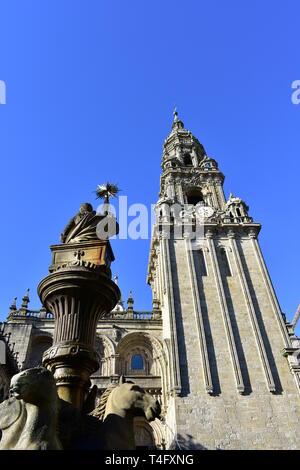Cathedral, romanesque Platerias facade and baroque clock tower with stone horses fountain and blue sky. Santiago de Compostela, Spain.