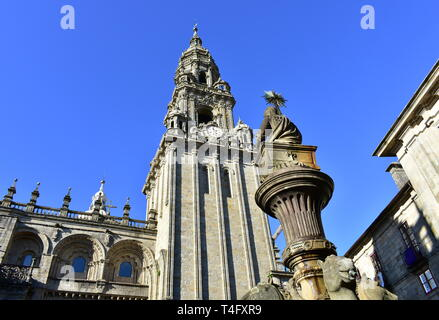 Cathedral, romanesque Platerias facade and baroque clock tower with stone horses fountain and blue sky. Santiago de Compostela, Spain. - Stock Photo