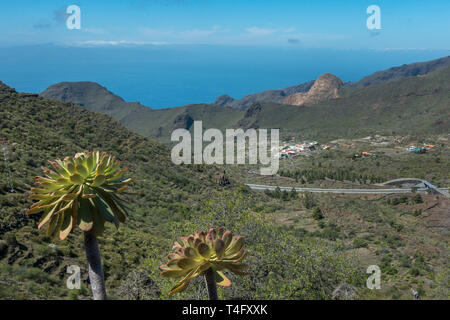 Beautiful landscape scenery with mountains and small village of El Molledo on the TF-82 mountain road (start of the TF-1 in the foreground), Tenerife - Stock Photo