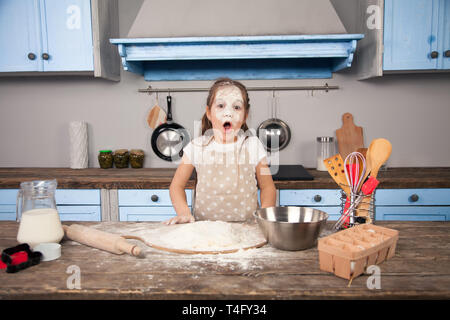 Little child daughter girl is helping her mother in the kitchen to make bakery, cookies. She has a flood all over her face. Fun cooking, homemade food - Stock Photo
