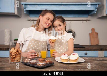 happy loving family in the kitchen. Mother and child daughter girl are eating cookies they have made and having fun in the kitchen. Homemade food - Stock Photo