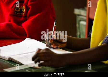 Close-up picture of child hands holding a pencil and writing down new information on the lesson at school. Clean paper in the notebook. Students - Stock Photo
