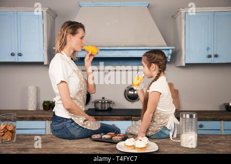 happy loving family in the kitchen. Mother and child daughter girl are eating cookies they have made with an orange juice sitting on the kitchen desk - Stock Photo