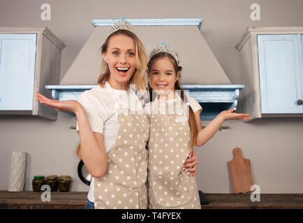 happy loving family in the kitchen. Mother and child daughter girl are having fun wearing crowns - Stock Photo