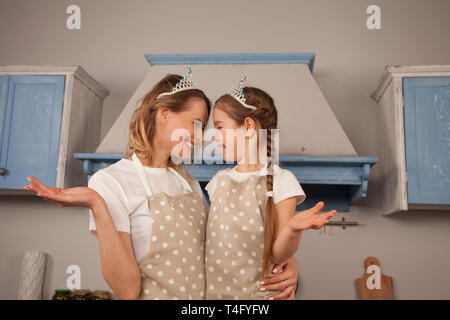 happy loving family in the kitchen. Mother and child daughter girl are having fun wearing crowns, looking at each other and smiling - Stock Photo