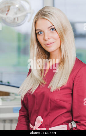 dentist woman in uniform standing in the dental office near the equipment. Concept Healthy - Stock Photo