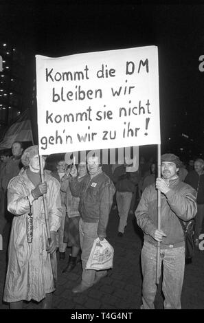 The picture shows a poster saying 'If the Deutsche Mark comes we will stay, if she doesn't come we will go to her' during a Monday demonstration in Leipzig on 12 February 1990. The demonstrators demand the introduction of the Deutsche Mark in the GDR which was put into effect in the scope of the economic, monetary and social union on 01 July 1990. It was one of the decisive steps towards the reunion of the two German states.   usage worldwide - Stock Photo