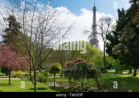 Eiffel tower near green park in Paris - Stock Photo
