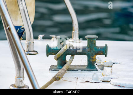 Close up of boat rope tied to nautical cleat hitch on boat - Stock Photo