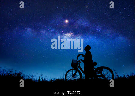 The boy is cycling in the midst of the stars galaxy - Stock Photo