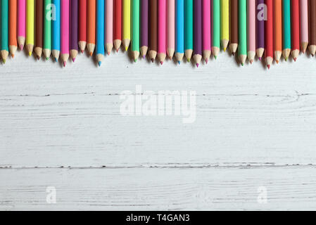 Colored pencils border on a wooden background, with copy space - Stock Photo