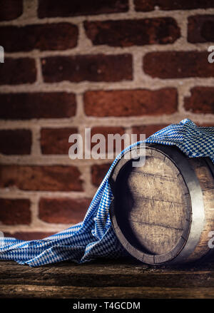 Oktoberfest wooden barrel and blue tablecloth on rustic oak table - Stock Photo