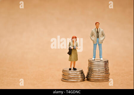 man and woman figurine standing on coins, gender pay gap concept - Stock Photo