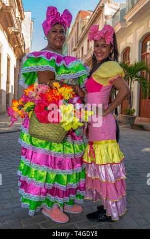 Cuban women with traditional floral  clothing posing for tourists in street in  Old Havana, Cuba - Stock Photo