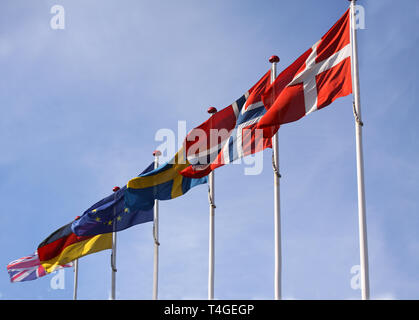 Flags from Denmark, Norway, Sweden, Germany and United Kingdom waving from flagpoles together with the EU, European Union, flag against a blue sky. - Stock Photo